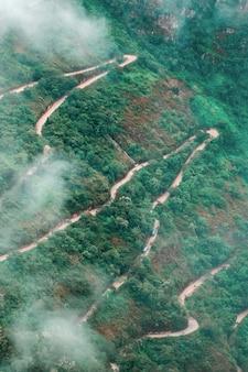 山の森林に覆われた蛇行道路の航空写真