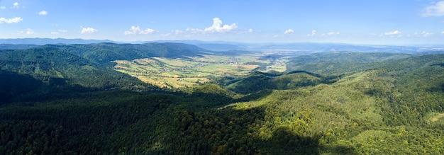明るい夏の日に密な緑豊かな森に覆われた山の丘の空撮。