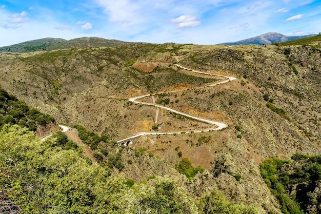 丘の中腹を曲がりくねった山道の空撮。スペイン。