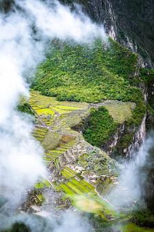 구름으로 덮인 산림이 우거진 마추픽추의 공중 전망