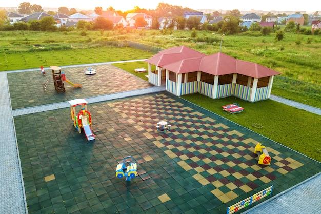 幼稚園の遊び場にある新しいアルコーブの空中写真。屋外の子供たちの活動のための赤い瓦屋根の遊び場。