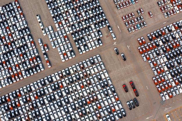 Аэрофотоснимок новых автомобилей на стоянке на автомобильном заводе.