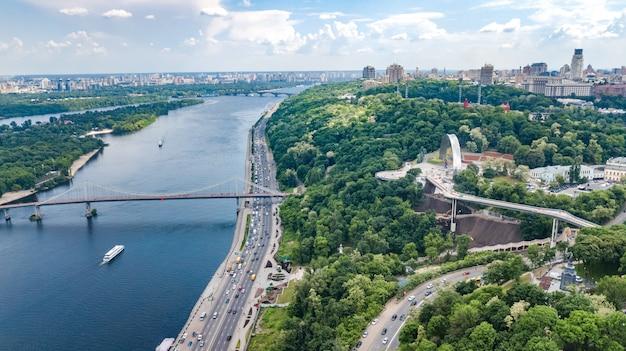 Аэрофотоснимок нового пешеходного велосипедного парка строительство моста, река днепр, холмы, парки и киевский городской пейзаж сверху, город киев, украина