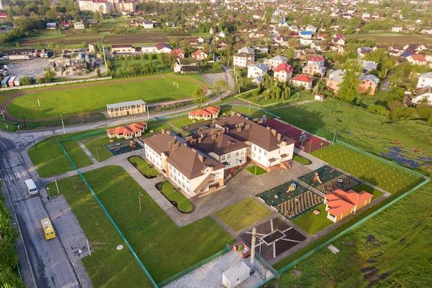 Вид с воздуха нового здания prescool в жилом сельском районе.