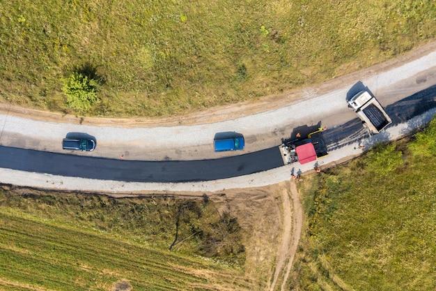 Аэрофотоснимок нового дорожного строительства с асфальтоукладчиками за работой.