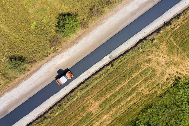 Аэрофотоснимок нового дорожного строительства с паровой роликовой машиной на работе.