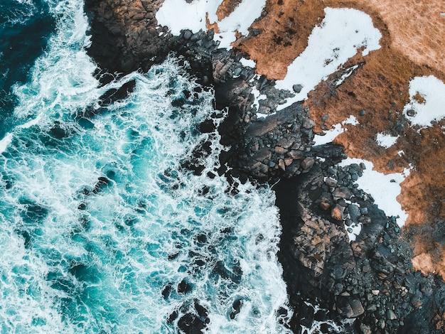 昼間に岩が多い海岸に打ち寄せる海の波の空撮
