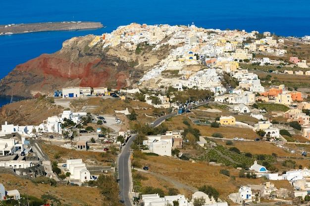 Вид с воздуха на ия или я и финикия на острове санторини, белые дома, ветряные мельницы и церковь с голубыми куполами, греция