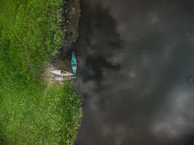 Вид с воздуха на старые деревянные лодки у берега реки в летний день
