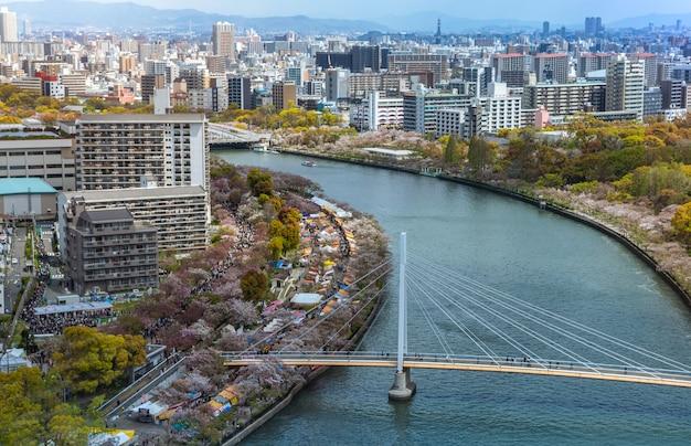 스카이 빌딩에서 오사카 시내와 강의 공중 전망. 붐비는 고층 빌딩 사무실과 아파트가 있는 도시 경관의 조감도. 일본 지구의 스카이라인에서 파노라마 도시 옥상 전망