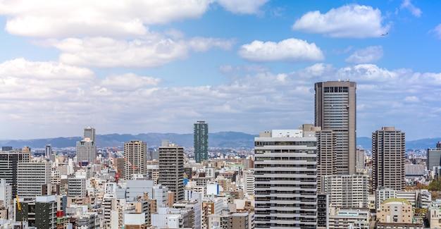 스카이 빌딩에서 오사카 시내의 공중 전망. 붐비는 고층 빌딩 사무실과 아파트가 있는 도시 경관의 조감도. 일본 지구의 스카이라인에서 파노라마 도시 옥상 전망