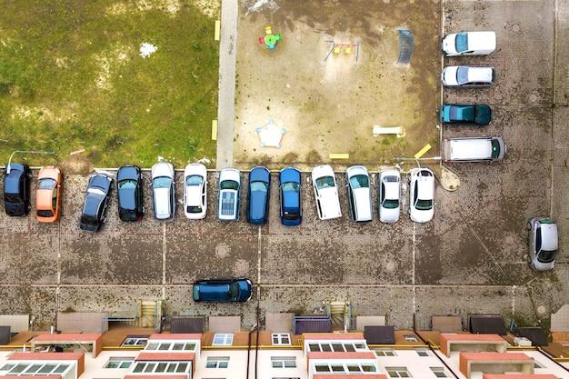 高いアパートの建物の間の駐車場に駐車した車の空撮。