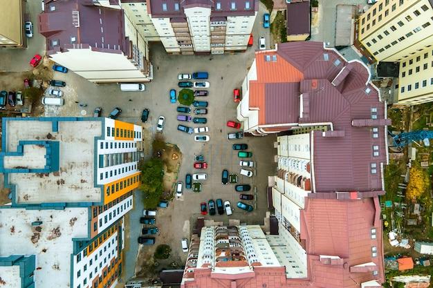 Вид с воздуха на припаркованные автомобили на стоянке между высокими многоквартирными домами.