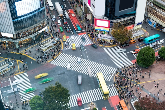 Вид с воздуха на пешеходов, идущих по перекрестку с людным транспортом на площади сибуя