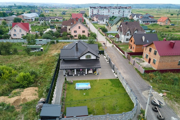 Вид с воздуха на частный дом с зеленым двором и небольшим бассейном на лужайке.