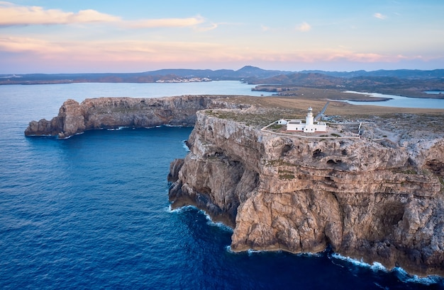 Вид с воздуха на маяк пунта-нати на менорке на вершине высоких скал у моря