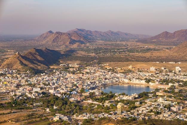 神聖な湖と周囲の丘と田園風景のある町、プシュカルの空撮