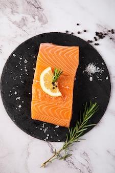 テーブルの上のレモンとローズマリーとスレートプレート上の生鮭の空撮