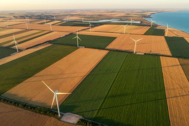 바다 옆 농업 초원의 광대 한 영역에서 부는 바람에서 에너지를 얻는 친환경 전력으로 재배 지역을 공급하는 재생 가능한 풍차 터빈의 공중보기. 대체 전기