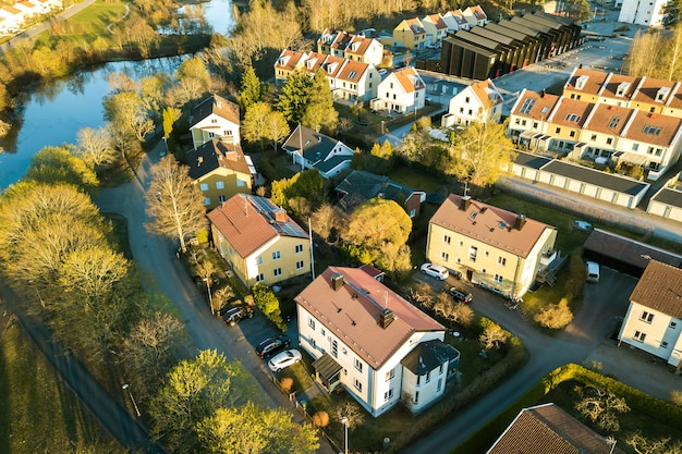 赤い屋根の住宅と田舎の町の駐車された車が付いている通りの空撮。近代的なヨーロッパの都市の静かな郊外。
