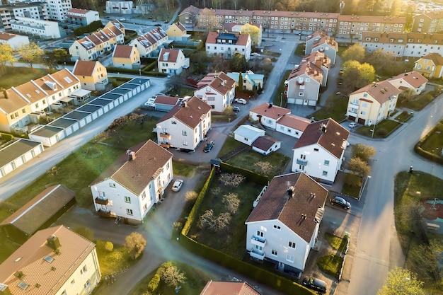 시골 마을 지역에 주차된 차가 있는 거리와 빨간 지붕이 있는 주거용 주택의 공중 전망.