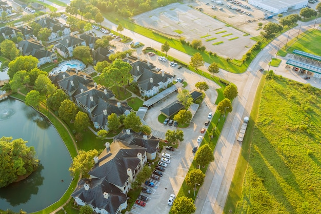 Вид с воздуха на жилые пригородные застройки во время осеннего заката в хьюстоне, штат техас, сша, возле пруда с тесно переполненными домами