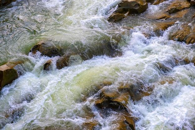 Вид с воздуха на речной водопад с чистой бирюзовой водой, падающей между мокрыми валунами с густой белой пеной.