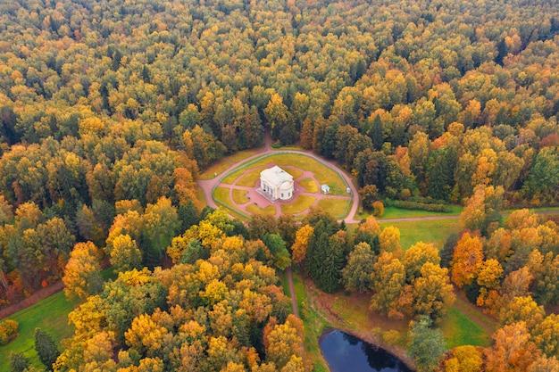 サンクトペテルブルク近郊の秋の木々に囲まれたパブロフスキー公園のラウンドホールビルの空撮。