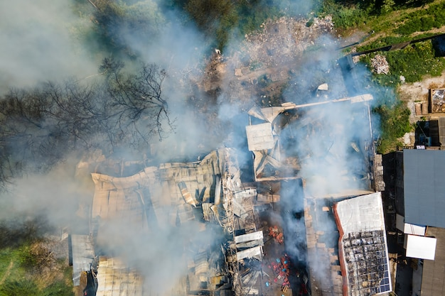 무너진 지붕과 치솟는 검은 연기로 불타고 있는 폐허가 된 건물의 공중 전망.