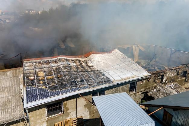 Вид с воздуха на разрушенное здание в огне с обрушившейся крышей и поднимающимся темным дымом.