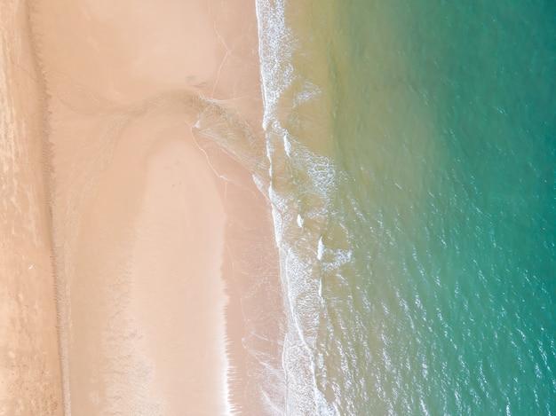 Вид с воздуха на песчаный пляж и океан с волнами