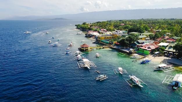 Oslob, 세부, 필리핀 근처 방문 sumilon 섬 해변의 아름 다운 맑은 바닷물에서 수영하는 관광객들과 모래 해변의 공중 전망. -컬러 프로세싱을 향상시킵니다.