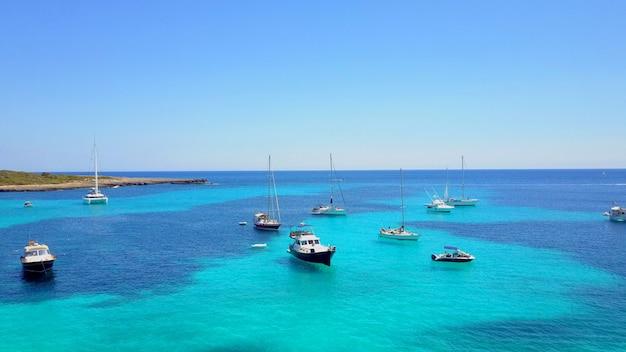 Вид с воздуха на побережье моря с лодками в менорка, один из балеарских островов, расположенных в средиземном море