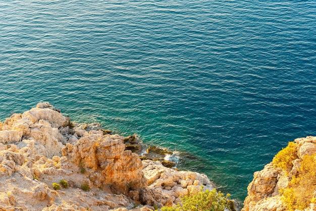 Вид с воздуха на морские волны и фантастическое скалистое побережье турции на рассвете.