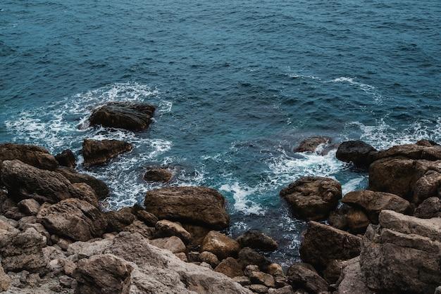 바다 파도와 바위 해안의 항공 보기