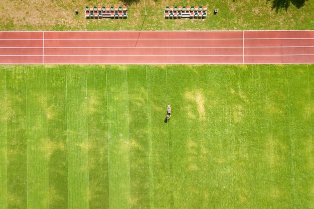 夏に赤いランニングトラックでサッカースタジアムのフィールドで芝刈り機で緑の草を刈る労働者の小さな図の空撮。