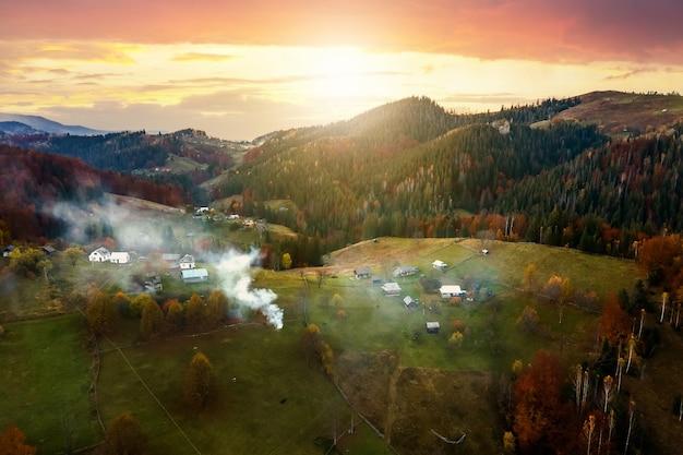 석양에 우크라이나 카르파티아 산맥의 가을 숲 사이의 넓은 초원에 있는 작은 양치기 집의 공중 전망.