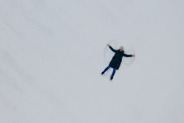 雪の中で若い女性によって作られたスノーエンジェルの空撮。上面図。
