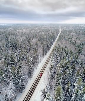 지나가는 자동차와 겨울 숲에서 눈 덮힌 도로의 공중보기