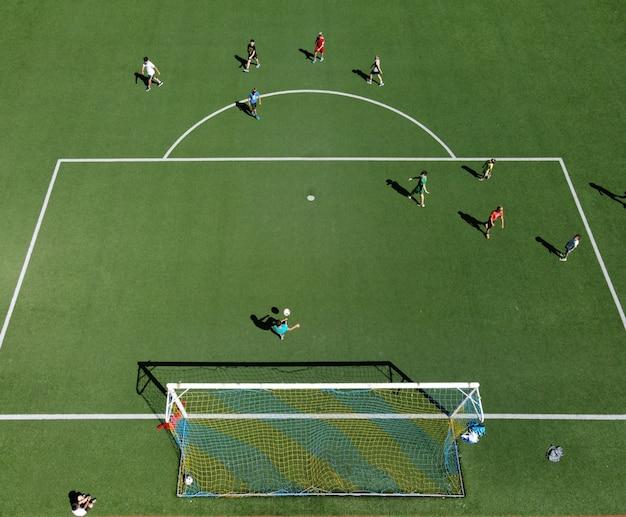 Вид с воздуха на футболистов на спортивном поле, играющих в футбол