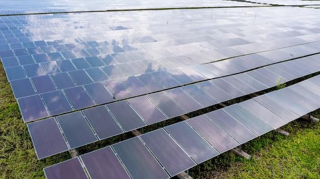 Аэрофотоснимок солнечных батарей или солнечных батарей на крыше фермы. электростанция с зеленым полем, возобновляемый источник энергии в таиланде Premium Фотографии