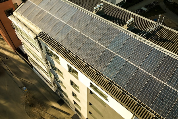 깨끗한 전기 에너지를 생산하기 위해 주거용 빌딩 블록의 옥상에 있는 태양광 패널의 공중 전망. 자치 주택 개념입니다.