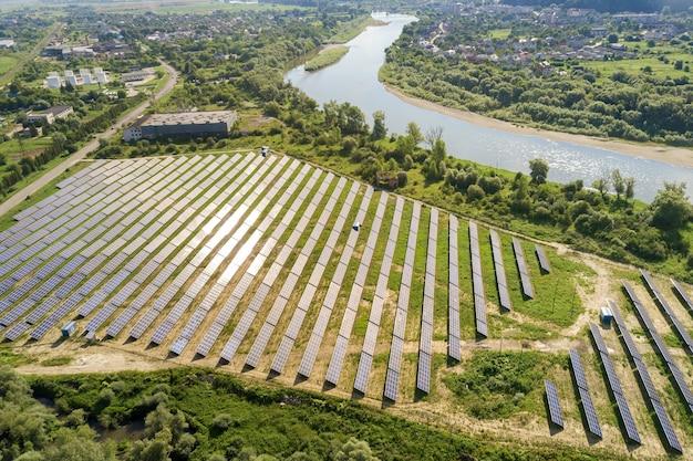 Аэрофотоснимок солнечной электростанции на зеленом поле. электрическая ферма с панелями для производства чистой экологической энергии.