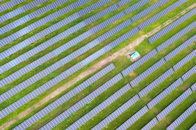 Аэрофотоснимок солнечной электростанции на зеленом поле. электрические панели для производства чистой экологической энергии.