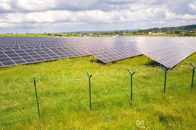 その周りに保護ワイヤーフェンスがある緑のフィールド上の太陽光発電所の航空写真。クリーンな生態学的エネルギーを生み出すための電気パネル。