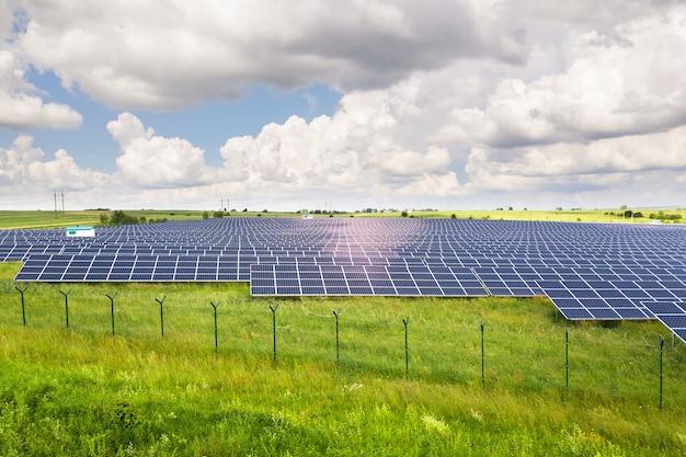 주위에 보호 와이어 울타리와 그린 필드에 태양 광 발전소의 공중 전망. 깨끗한 생태 에너지를 생산하기위한 전기 패널.