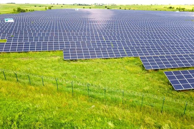 주위에 보호 철조망이 있는 녹색 들판에 있는 태양광 발전소의 공중 전망. 깨끗한 생태 에너지를 생산하기 위한 전기 패널.