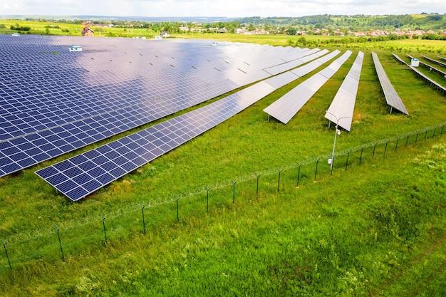 Вид с воздуха на солнечную электростанцию на зеленом поле с защитным проволочным забором вокруг него.