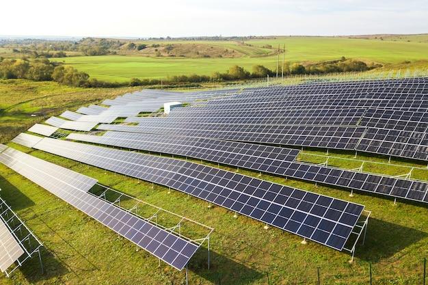 Вид с воздуха на строящуюся солнечную электростанцию на зеленом поле сборка электрических панелей для производства чистой экологической энергии