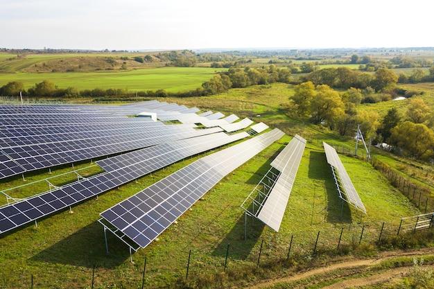 グリーンフィールドに建設中の太陽光発電所の航空写真。クリーンな生態学的エネルギーを生み出すための電気パネルの組み立て。
